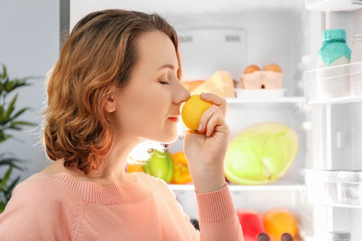A woman smells a lemon from her refrigerator. Limonene is a terpene that creates the unique smell of citrus fruits.