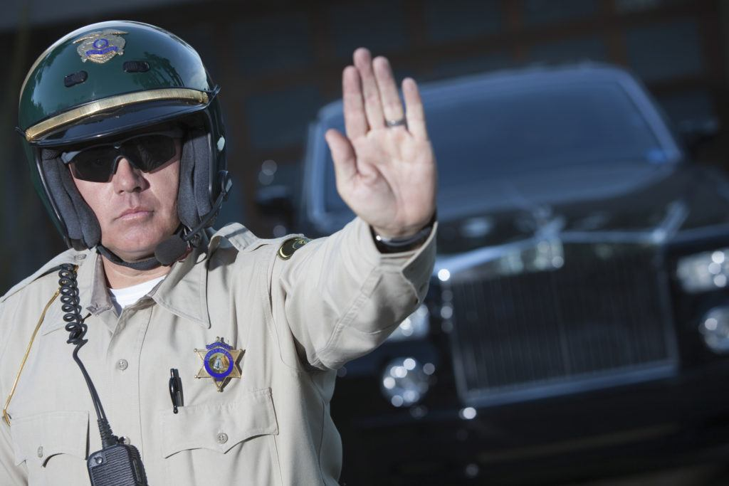 A highway patrol officer holds his palm out while making a road side stop. Oklahoma police seized 18,000 pounds of hemp and charged four people with felony drug trafficking crimes for transporting legal hemp.