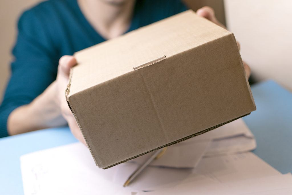 Point of view photo of a person mailing a cardboard box hands it off to a worker. Recent court rulings make it clear it's fully legal to send hemp by mail.