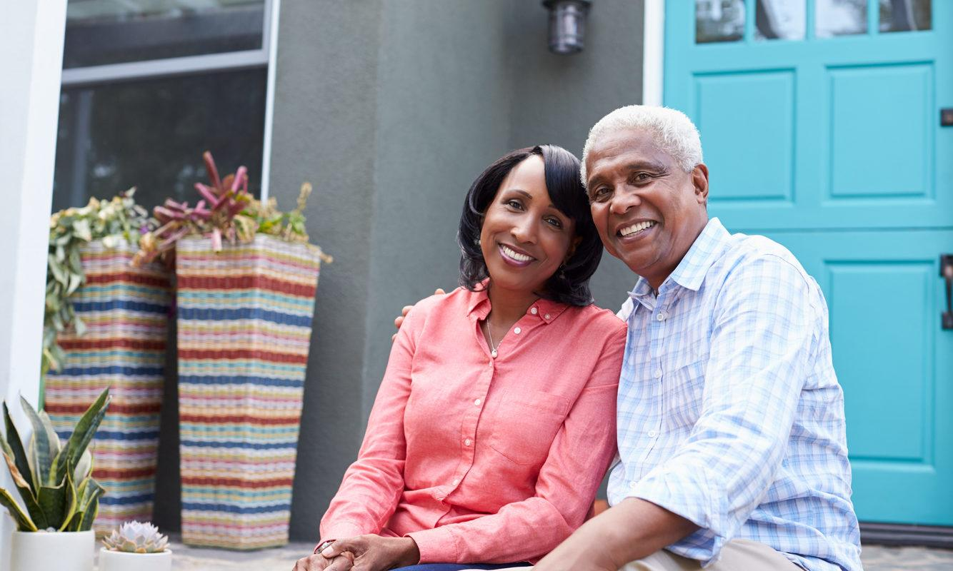 A woman and man, a senior citizen couple, sit outside their home. He has his arm around her. There are numerous benefits of CBD for senior citizens, from reducing inflammation to easing anxiety.