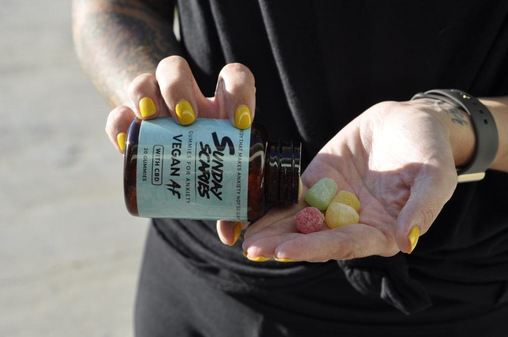 A person in dark clothes with bright yellow nail polish pours Sunday Scaries Vegan AF CBD Gummies into the palm of their hand. We found these gummies delicious and relaxing, with a clever branding that made us laugh.