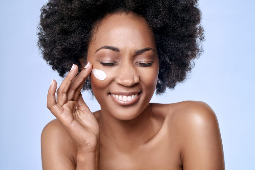 A black woman smiles with her eyes closed as she applies moisturizer to her cheek. More people are using hemp oil in skincare because of its numerous benefits.