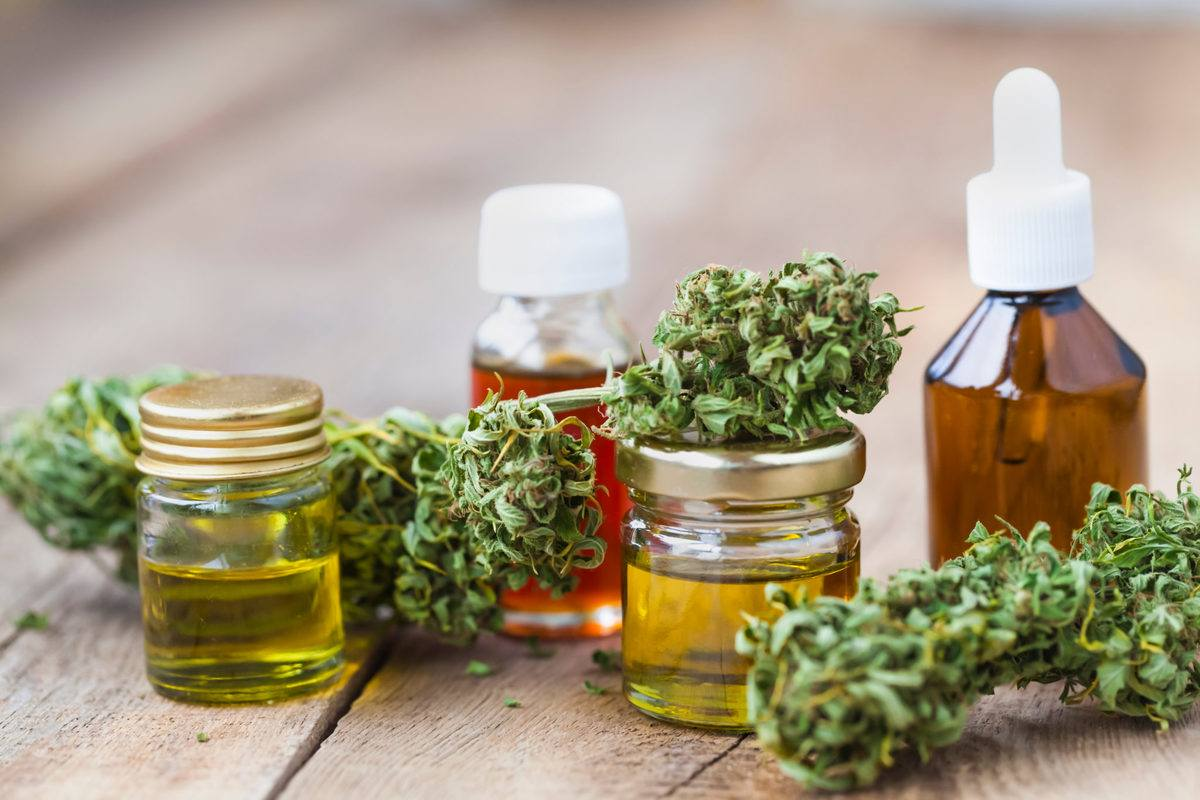 A collection of CBD tinctures in assorted bottles, decorated with hemp buds. Our guide to CBD tinctures explains how to pick the right supplement for your needs.