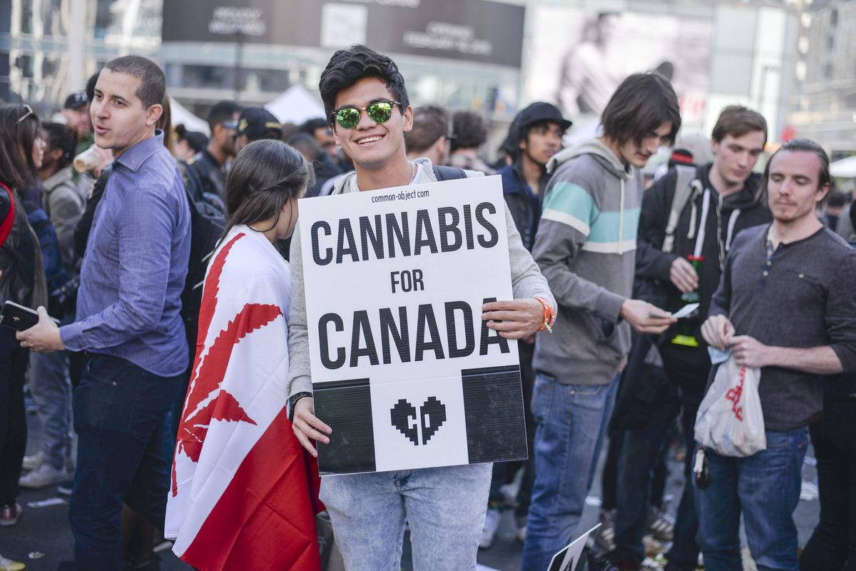 "An activist holds a ""Cannabis for Canada"" sign at a 420 celebration. Despite legalization of recreational cannabis, it's still difficult to obtain legal CBD in Canada."