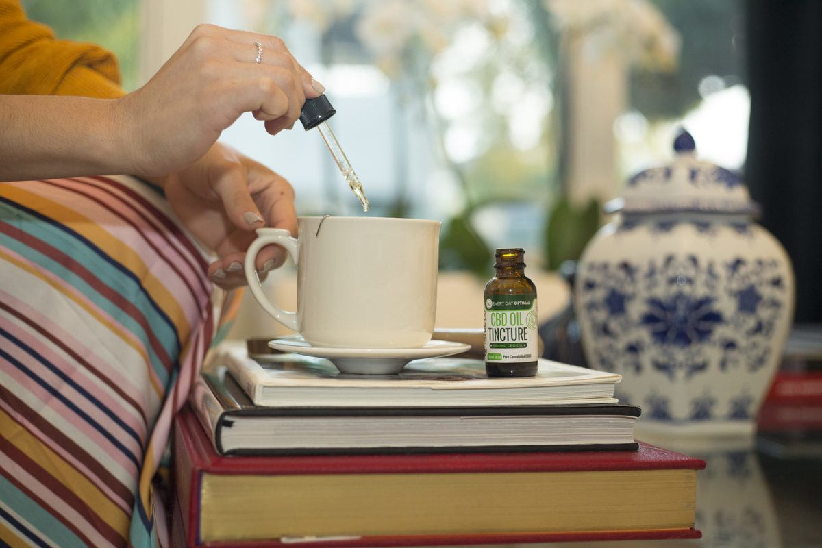 A seated person stirs Every Day Optimal CBD Oil into a cup of tea. When it comes to chronic pain, there's no clear winner in the CBD vs. THC debate: both have their uses.