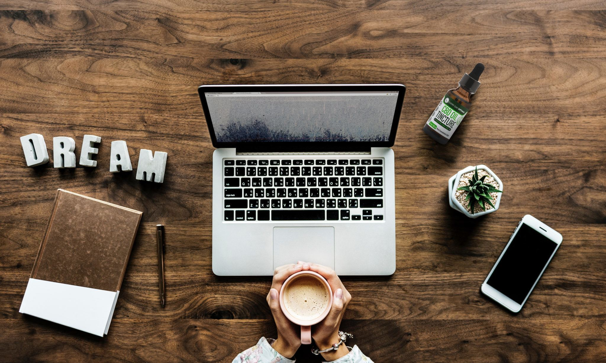 In this article, we compare the benefits of CBD vs. CBN and explain how both can help us live better lives. A seated person cups a mug of coffee in their hands in front of a laptop. Arranged nearby are a small plant, a notepad, a smartphone, a bottle of Every Day Optimal CBD, and decorate letters spelling the word DREAM.