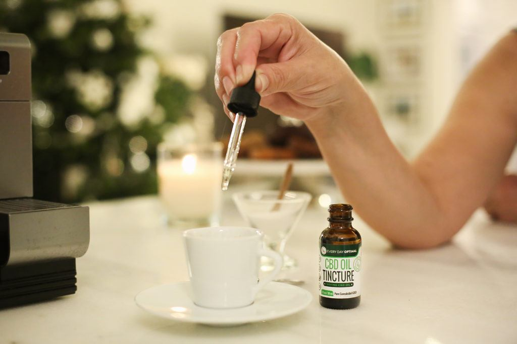 In this article we compare CBD vs. CBN for their different health benefits. A person drops a dropperful of CBD oil from a bottle of Every Day Optimal into a cup of espresso.