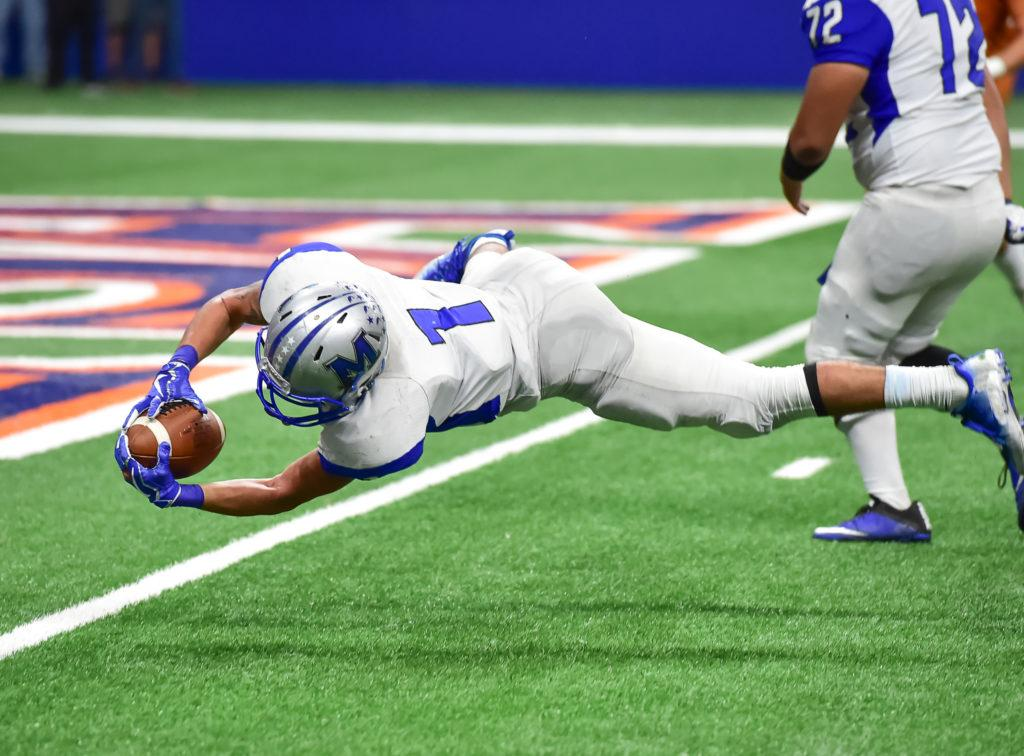 A professional football player dives for the end zone while holding a football, dressed in a helmet and other typical gear. There's a complex relationship with CBD in professional sports, thanks to complex and changing regulations around all forms of cannabis.