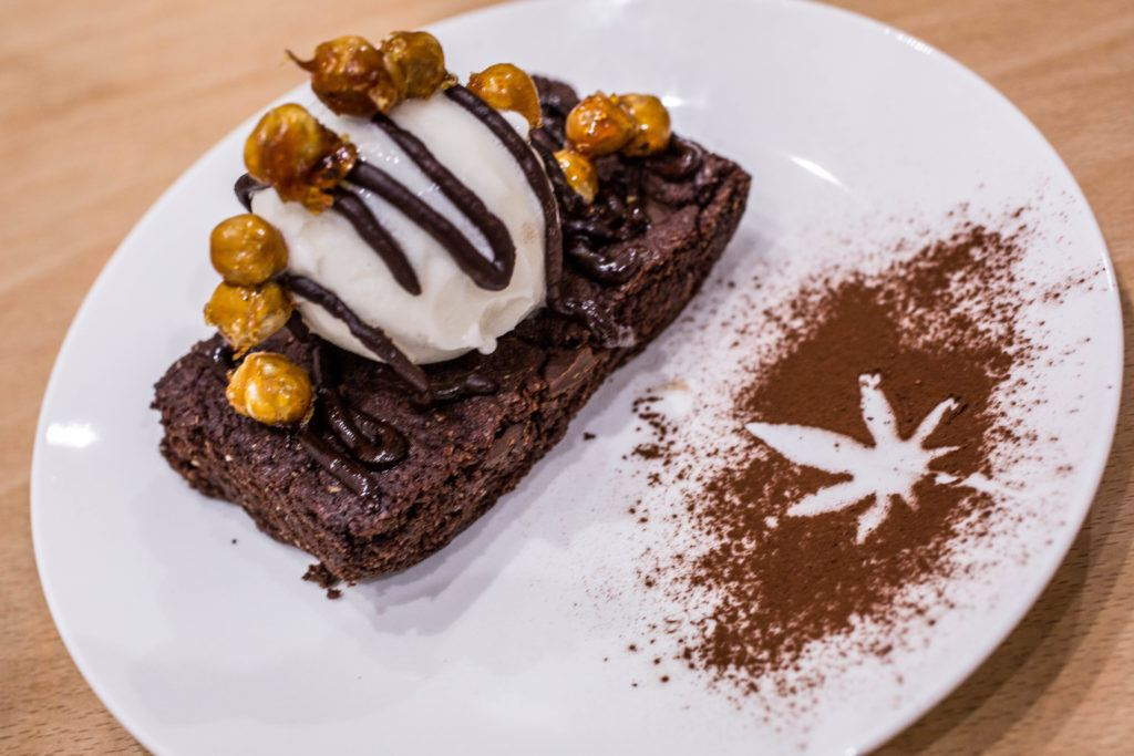 A decadent CBD-infused chocolate brownie a la mode, on a white plate decorated with a hemp leaf drawn in cocoa powder. The Canna Kitchen is the UK's first CBD restaurant, and it's making waves for their delicious vegetarian food.