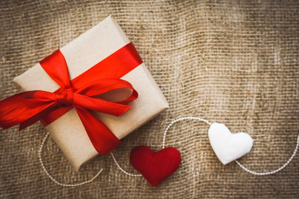 A gift wrapped with a red ribbon and decorated with hearts on a string, sitting on a fabric background. Our Valentine's Day CBD Gift Guide can make your holiday more relaxed, healthier, and more romantic too.