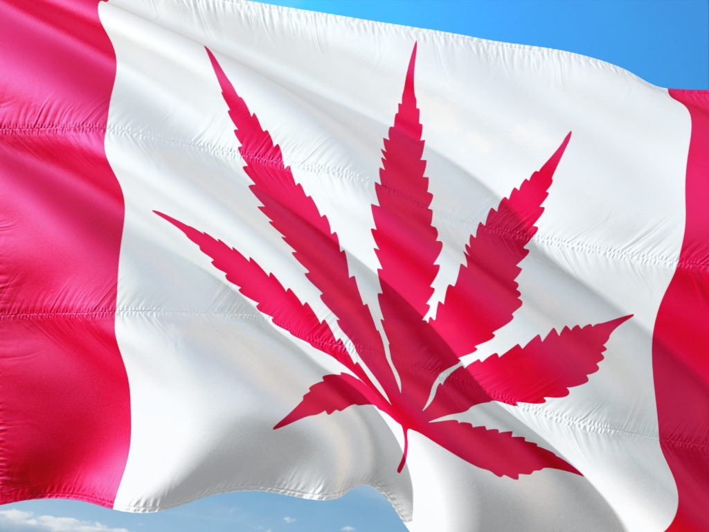 A photo of an altered Canadian flag flying against a blue sky. The typical maple leaf is replaced with a hemp or cannabis leaf. Despite cannabis legalization, access to legal CBD in Canada remains challenging.