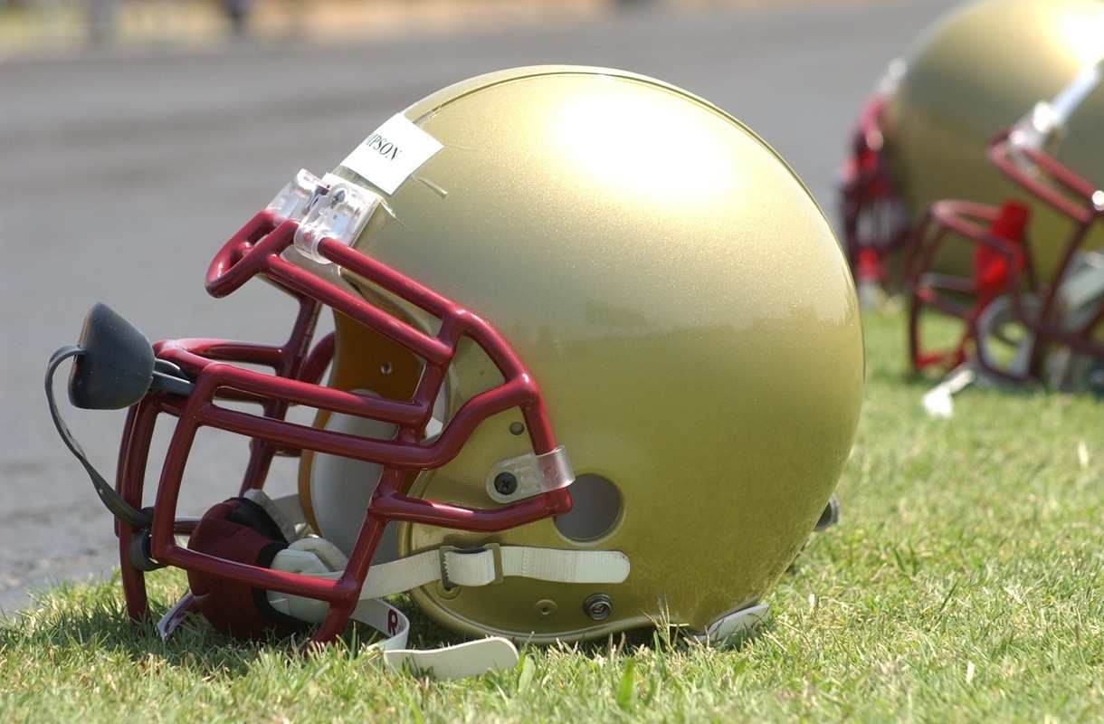 Football helmets sit on a football field. Despite advances in safety gear, football players still face repeated injuries and treatment can leave them addicted to painkillers.