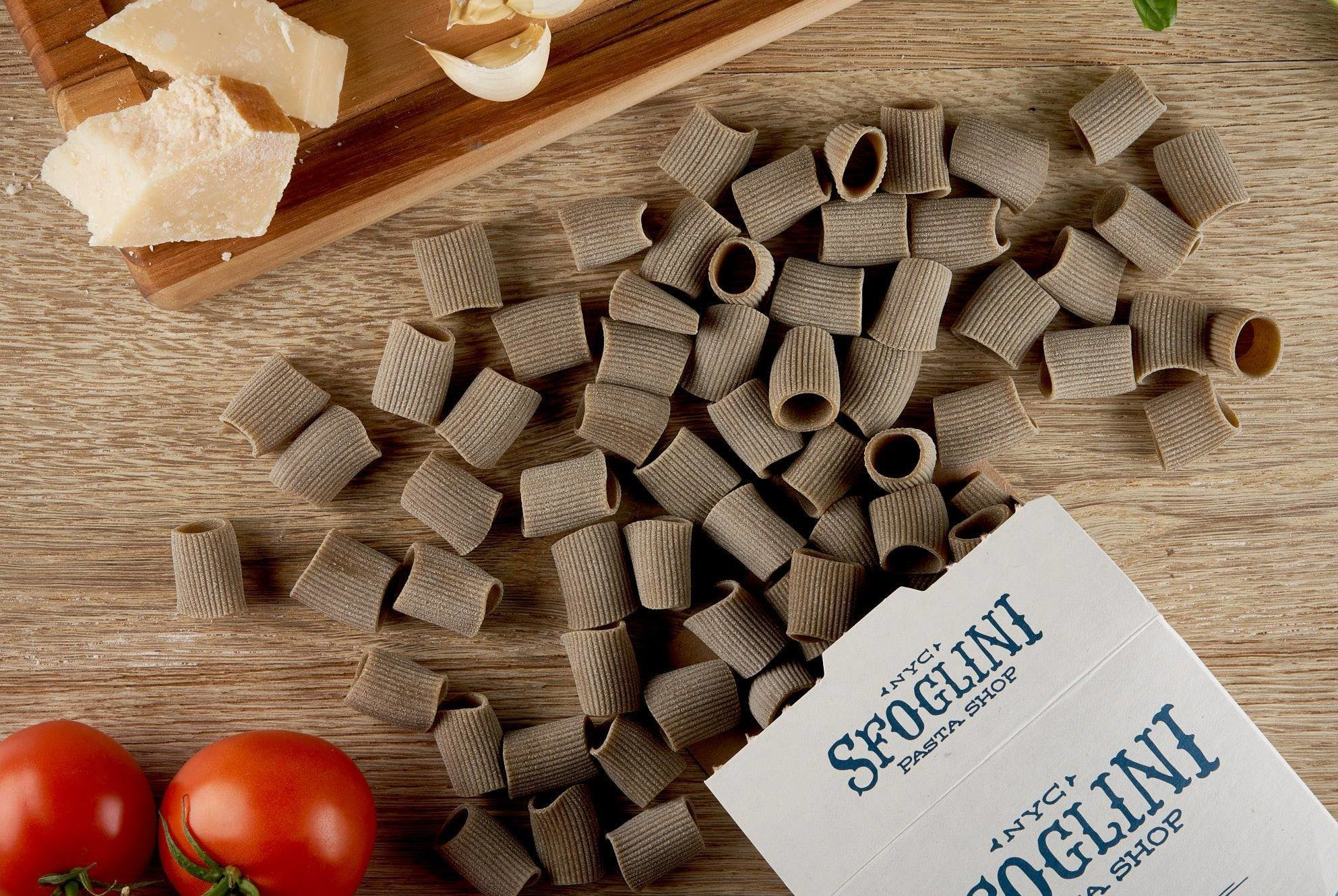 Sfoglini Hemp Pasta spills out onto a kitchen counter, with other ingredients neabry including tomatoes, Parmesan cheese and garlic. Sfoglini's hemp pasta joins a unique product line that includes season flavors like Beet Fusilli, Cuttlefish Ink Spaccatelli, and Saffron Malloreddus.
