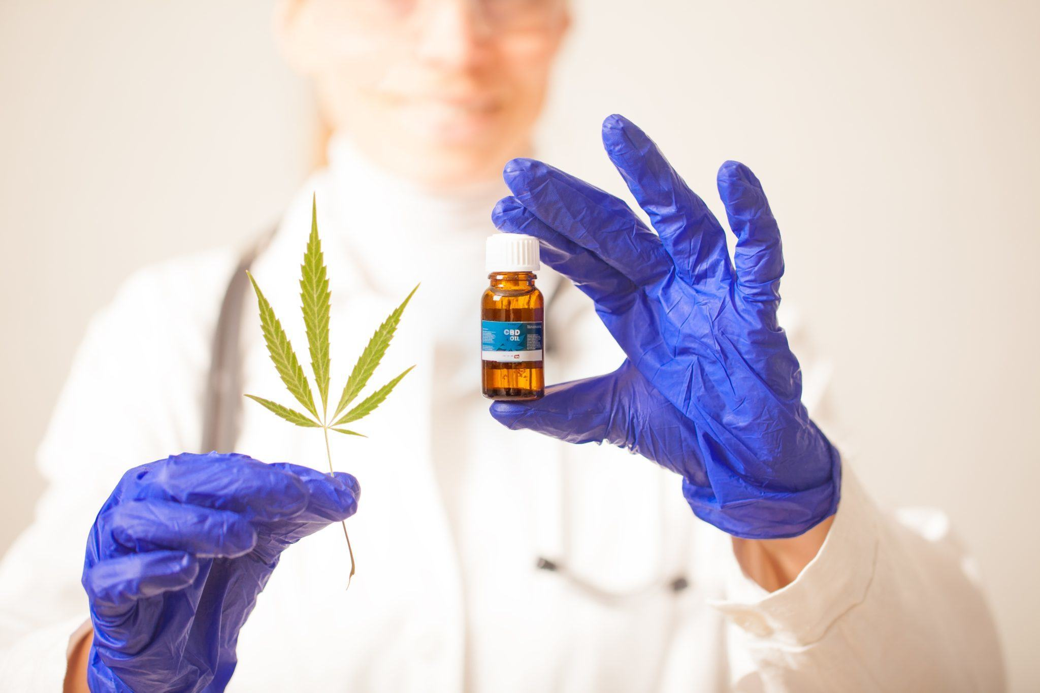There's growing demand on cannabis & hemp product testing labs, but also renewed attention on their inconsistencies too. Photo: A gloved scientist with a vial of CBD and a hemp leaf.