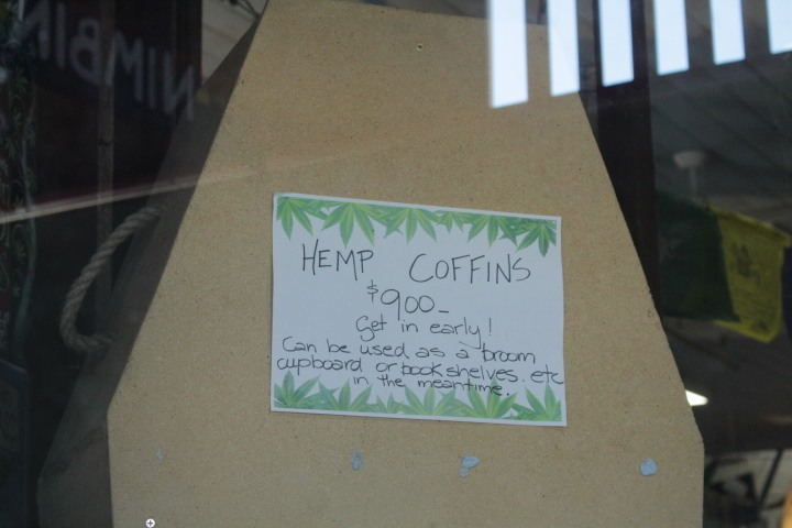 A sign on a hemp coffin suggests they can be used to store books or cleaning supplies before death.