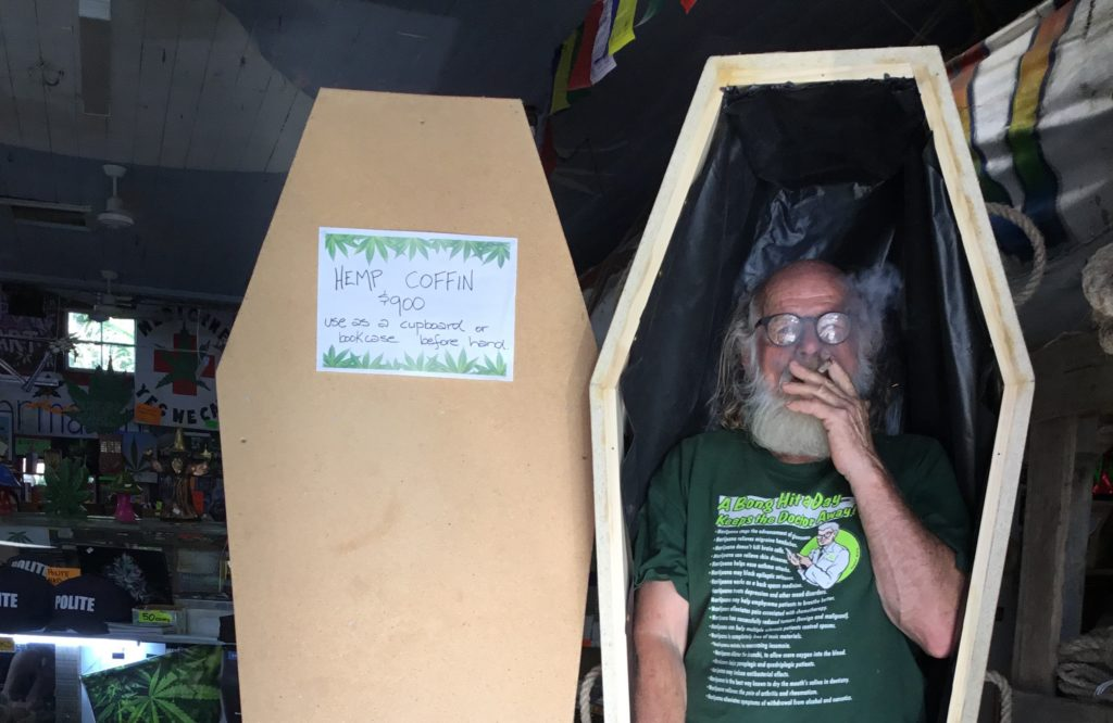 A man smokes a joint while standing in an undecorated hemp coffin, at the Hemp Embassy in Nimbin, New South Wales, Australia.