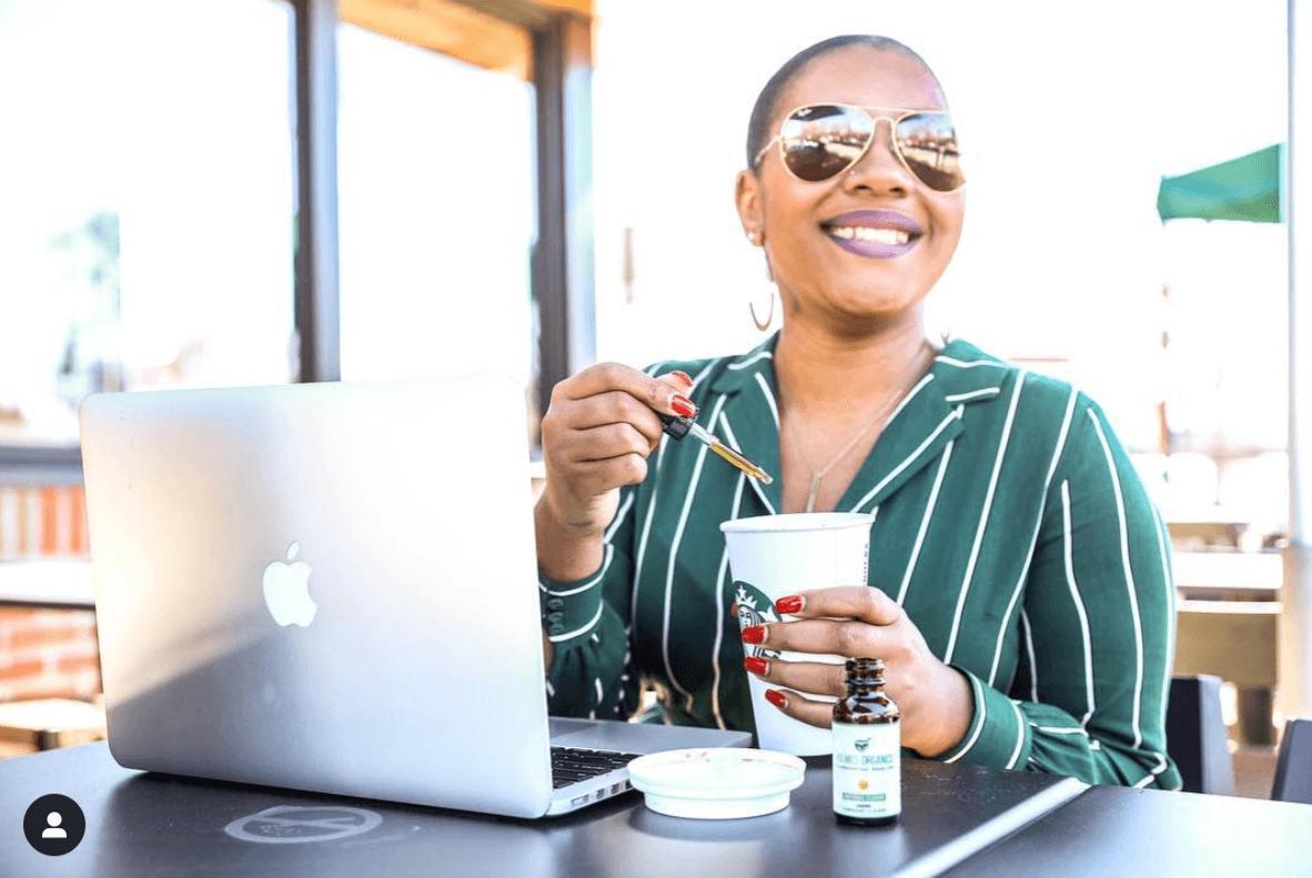 A woman using a laptop drops Holmes Organics CBD Tincture