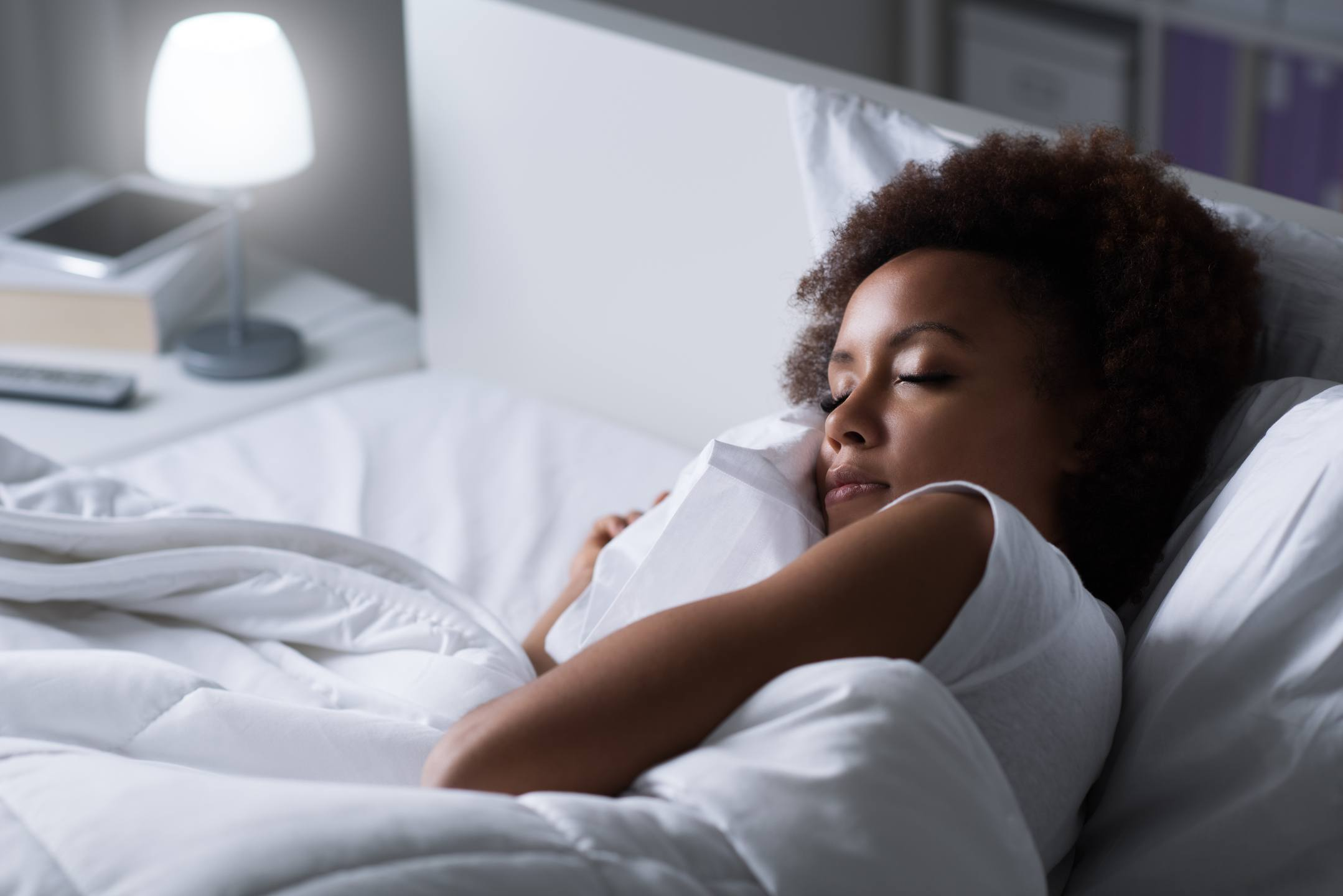 An increasing body of research supports using CBD for sleep and insomnia treatment. Photo: A dark-skinned woman sleeps on a bed with white sheets, while a light shines on a nightstand.