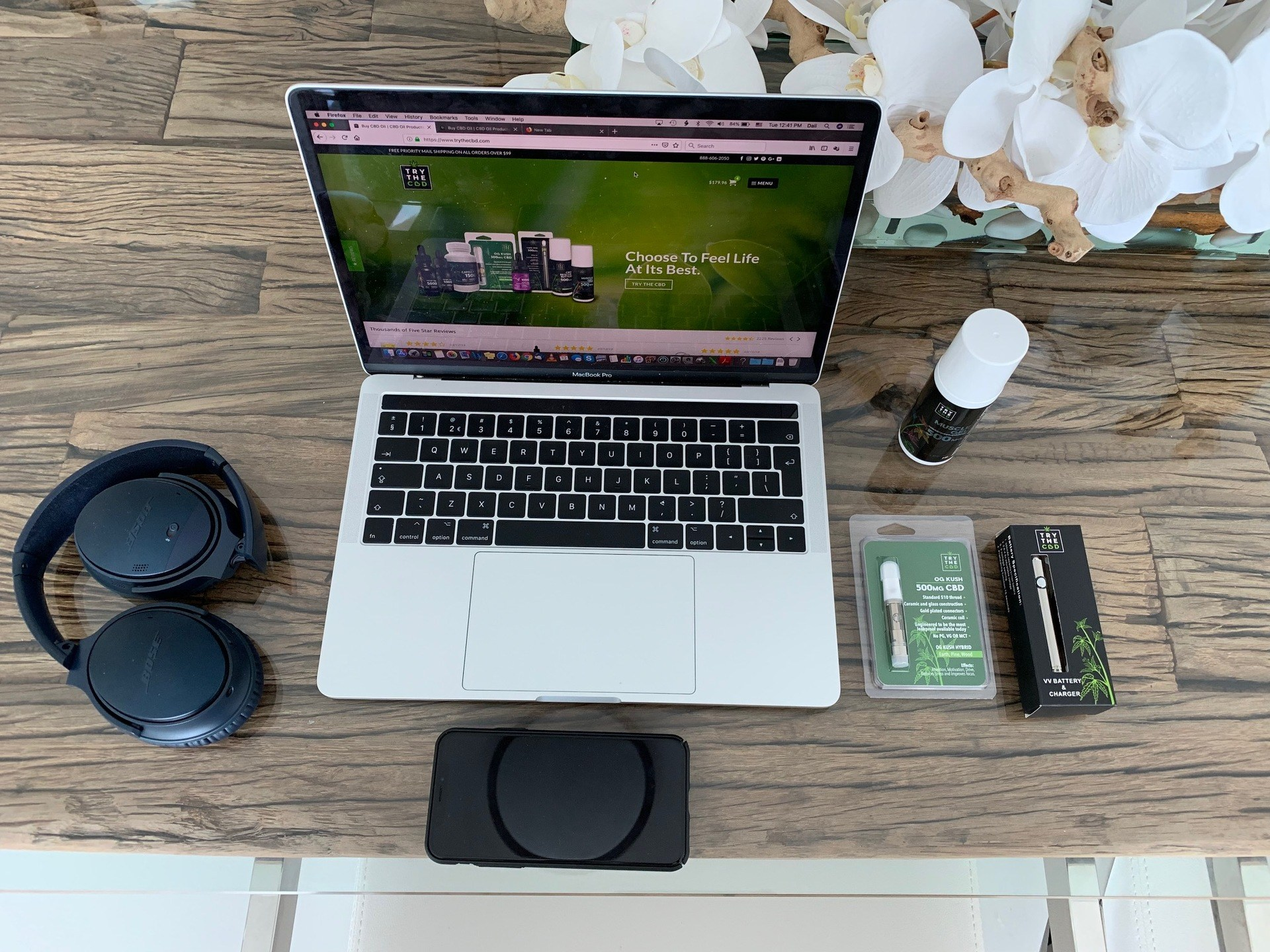 TryTheCBD Vape Cartridges combine CBD isolate with plant-based terpenes in a special carrier fluid free of common irritants, for smooth delicious vaping. Photo: TryTheCBD Vape Cartridges and other TryTheCBD products posedaround a laptop on a wooden desk, with headphones nearby.