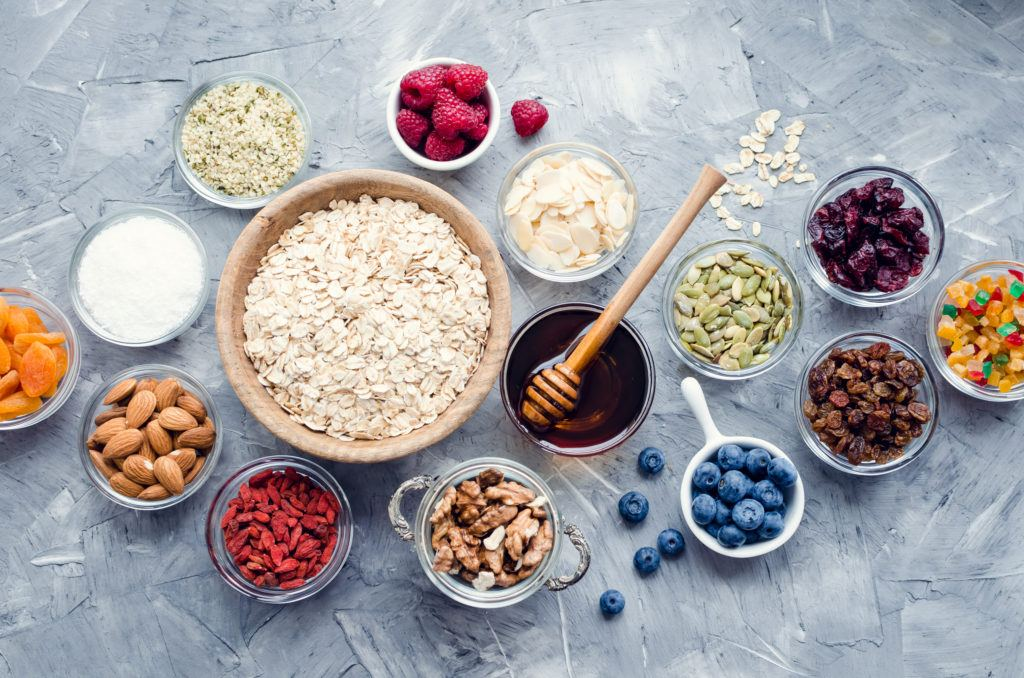 Delicious, nutritious, and easy to customize, our hemp granola recipe will be your new easy breakfast snack. Photo: Various granola ingredients in bowls including oats, hemp hearts, honey, nuts, and berries.