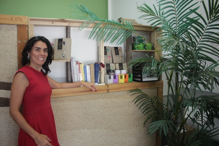 Maxine Shea poses with a collection of Hemp Collective products and a small hempcrete wall.