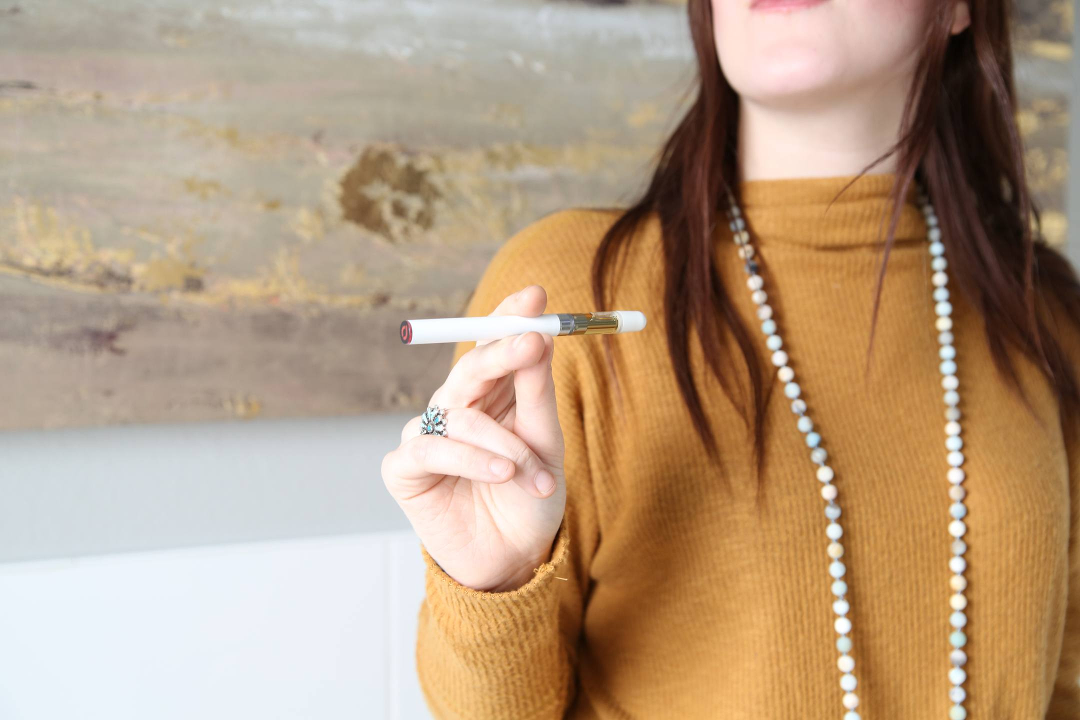 A brunette woman in an orange sweater and long pearl necklace holds an elegant Joy Organics CBD vape pen in one hand.