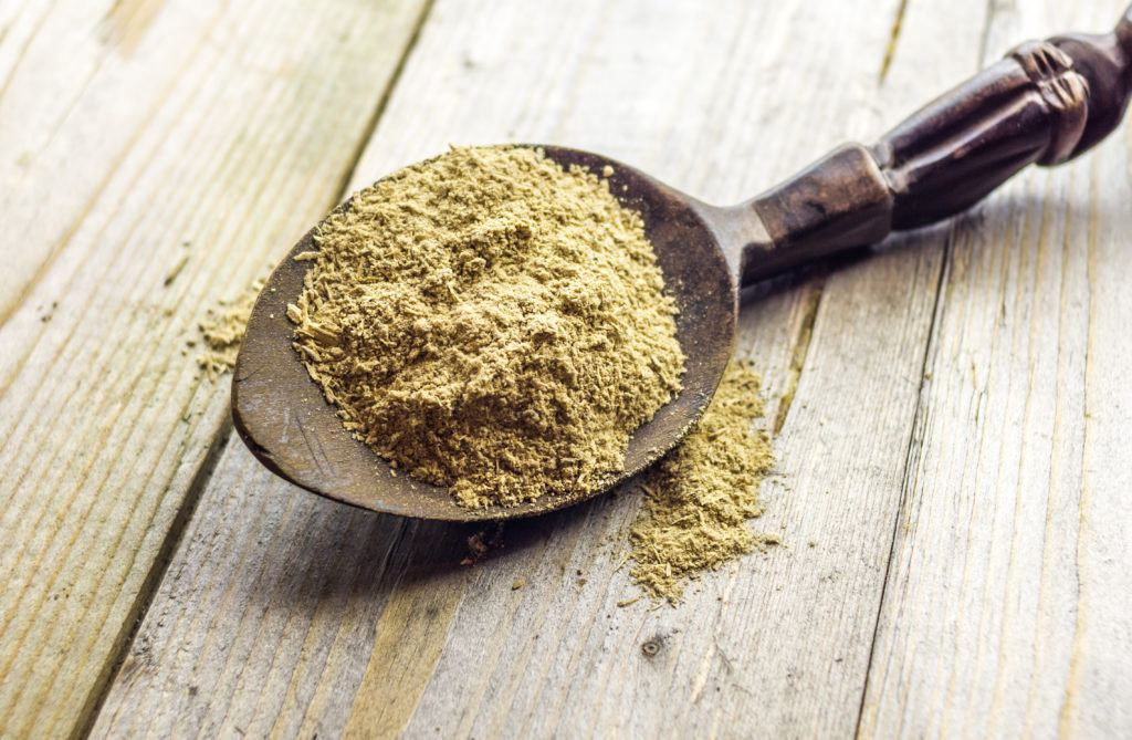 We compared the relative benefits of CBD and kava kavas. Photo: A spoonful of powdered kava root resting on a wooden table.