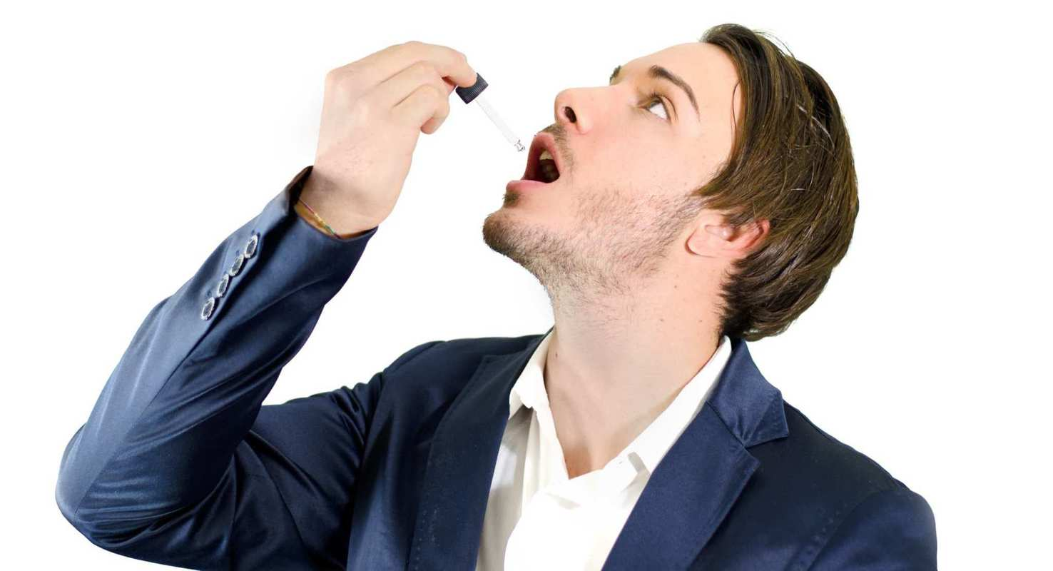 Sublingual CBD has high bioavailability. Photo: A man takes a tincture.