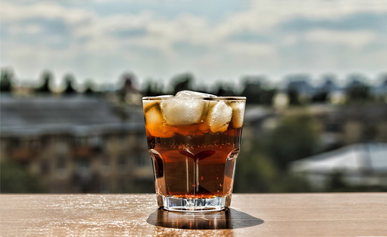 Even the water used by Wee Hemp Spirits is carefully selected to enhance the flavor and effectiveness of their CBD liquor. Photo: A rum and coke with ice in a lowball glass, sitting on a table at the edge of a blurry nature scene.