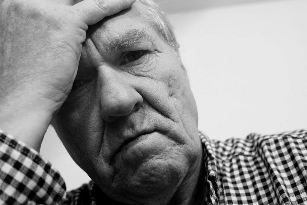 Photo: An older man in a checked button down shirt holds his forehead in despair.