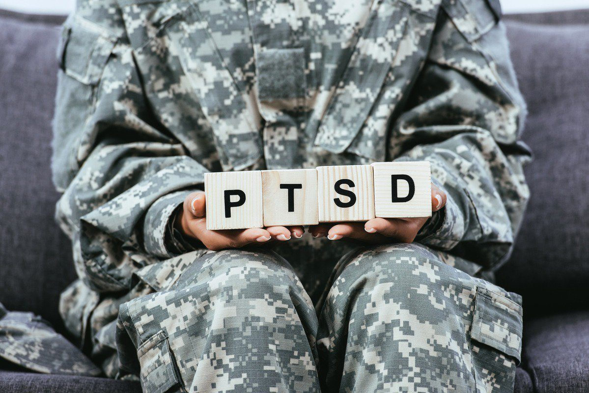 Using CBD for PTSD can ease some of this complex condition's most troubling symptoms. Photo: Cropped shot of female soldier in military uniform sitting on sofa and holding wooden cubes that spell PTSD.