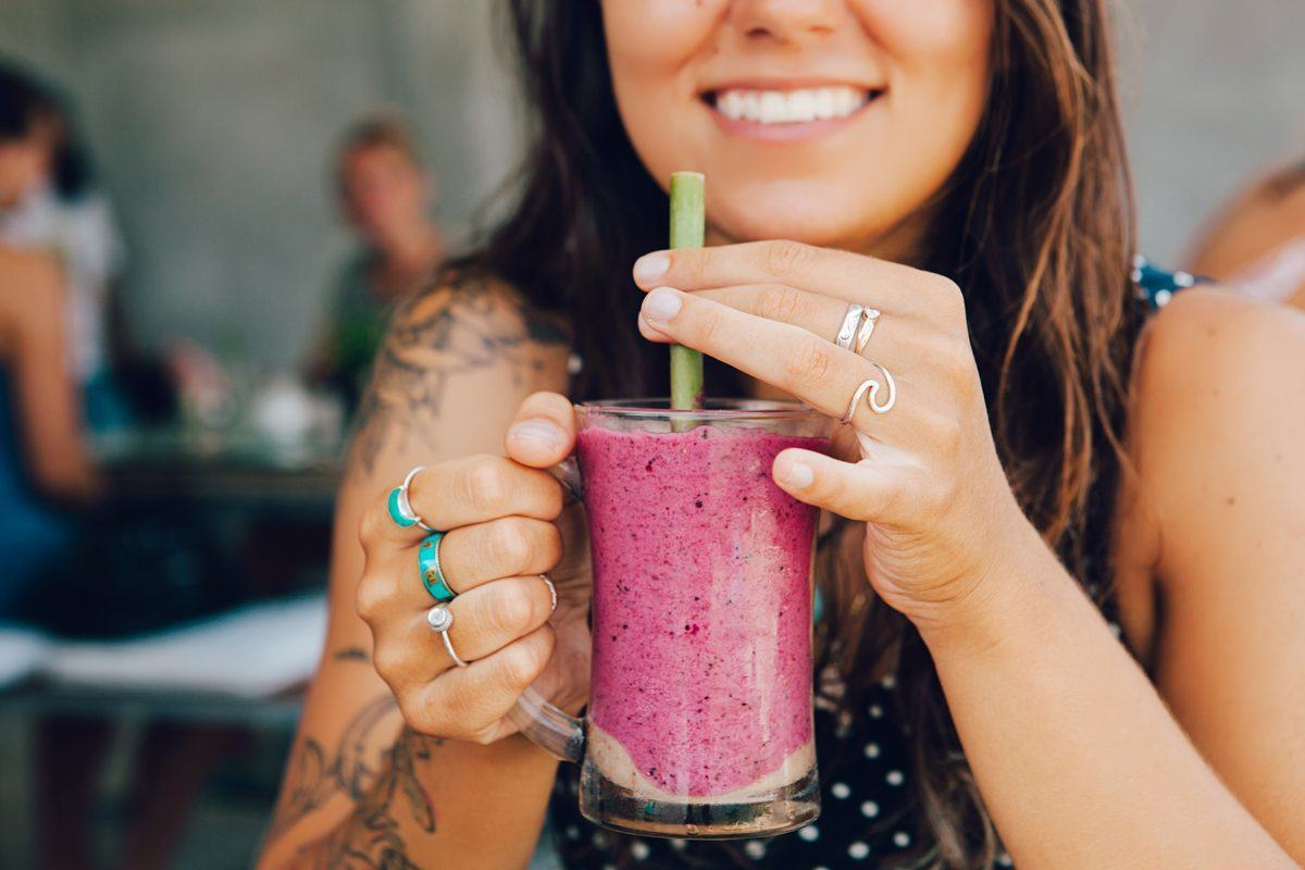 A smiling woman enjoys a easy hemp protein smoothie from a glass mug, with a straw.