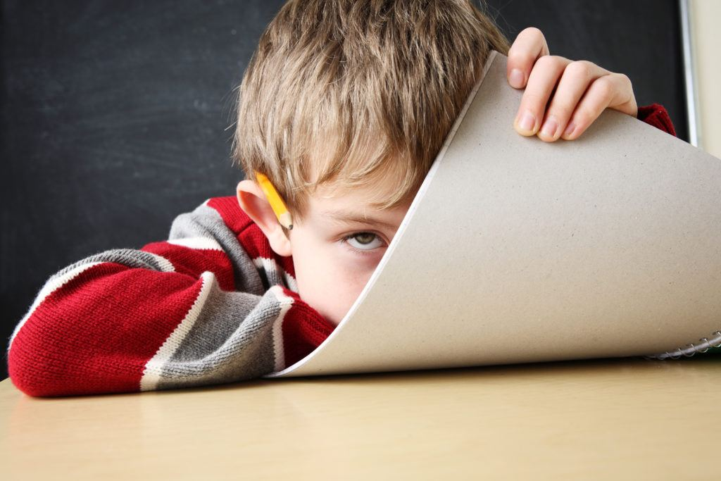A young student hides playfully behind a piece of posterboard while sitting at a desk. Some research supports using cannabinoids like CBD for ADHD.
