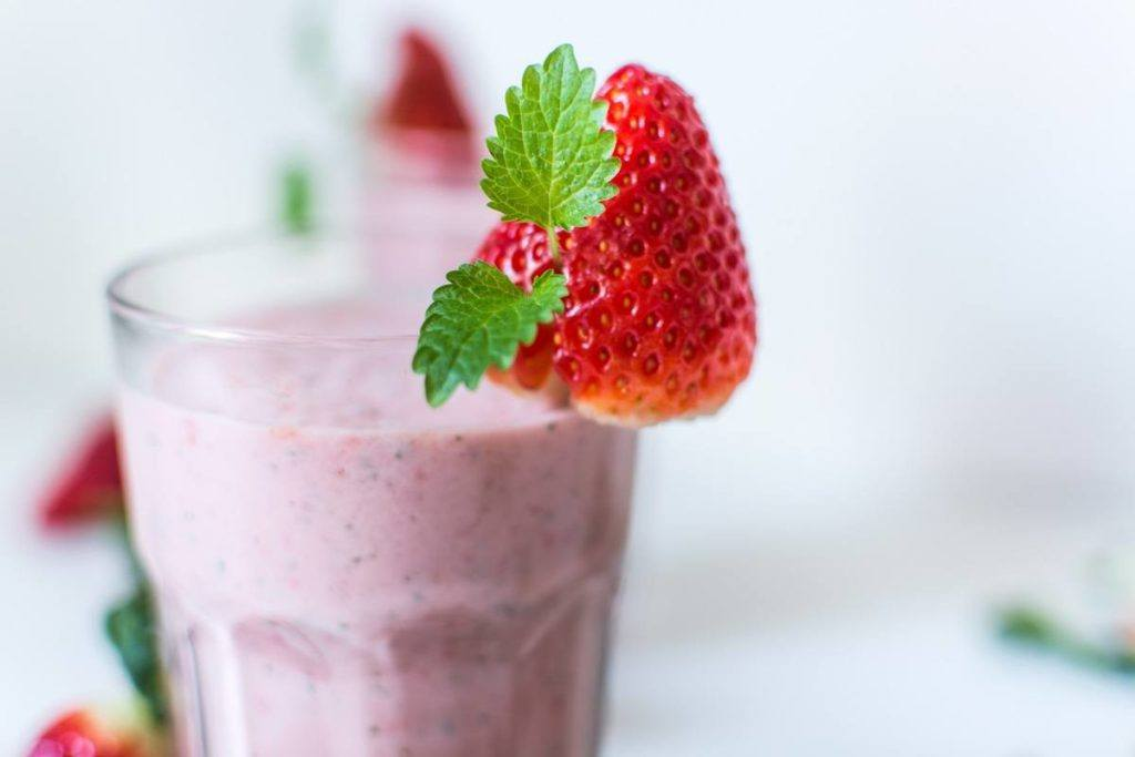 A berry hemp protein smoothie in a drinking glass, garnished with a strawberry.