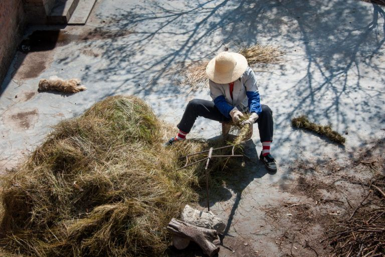 Seated on the ground, a Chinese worker collects hemp twine for rope. China is the world's leading provider of hemp and hemp-based products.