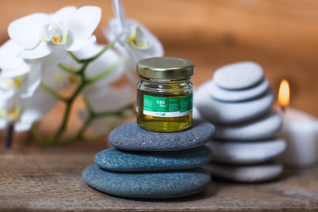 How long does it take for CBD to work? It depends on the method of ingestion. Photo: A generic bottle of CBD oil sits atop a stack of flat rocks with a candle and flowers in a meditative looking display.