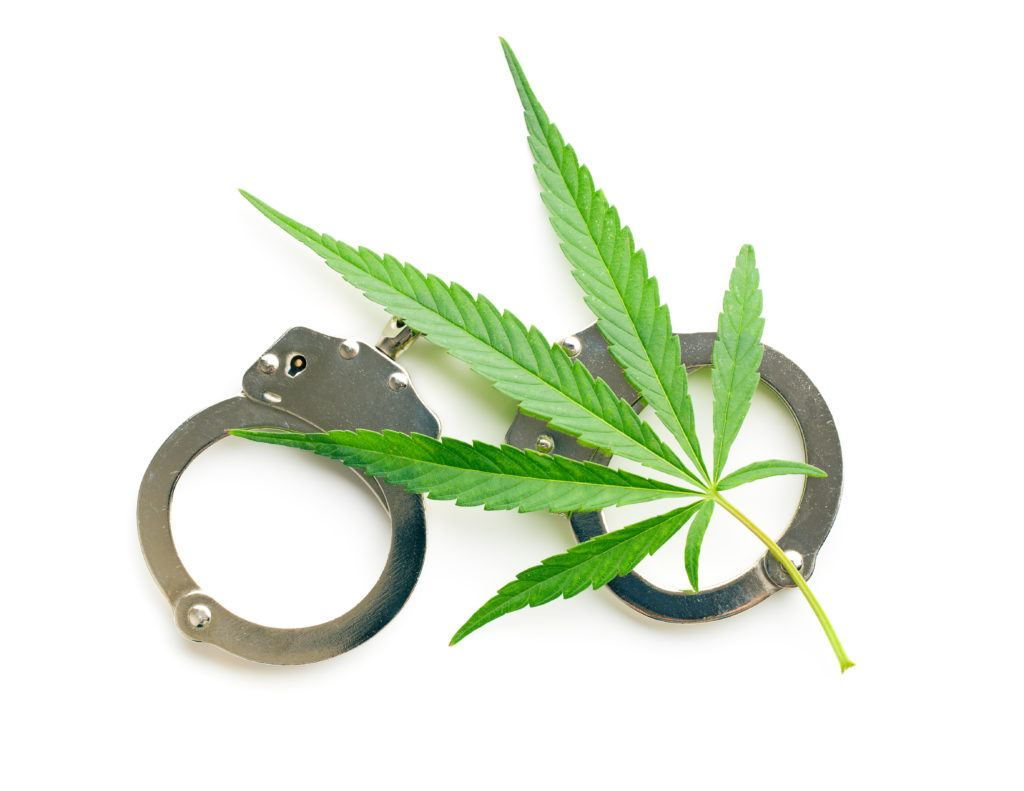 Despite the 2018 Farm Bill, some people still get arrested over hemp. Photo: A hemp leaf with a pair of handcuffs.