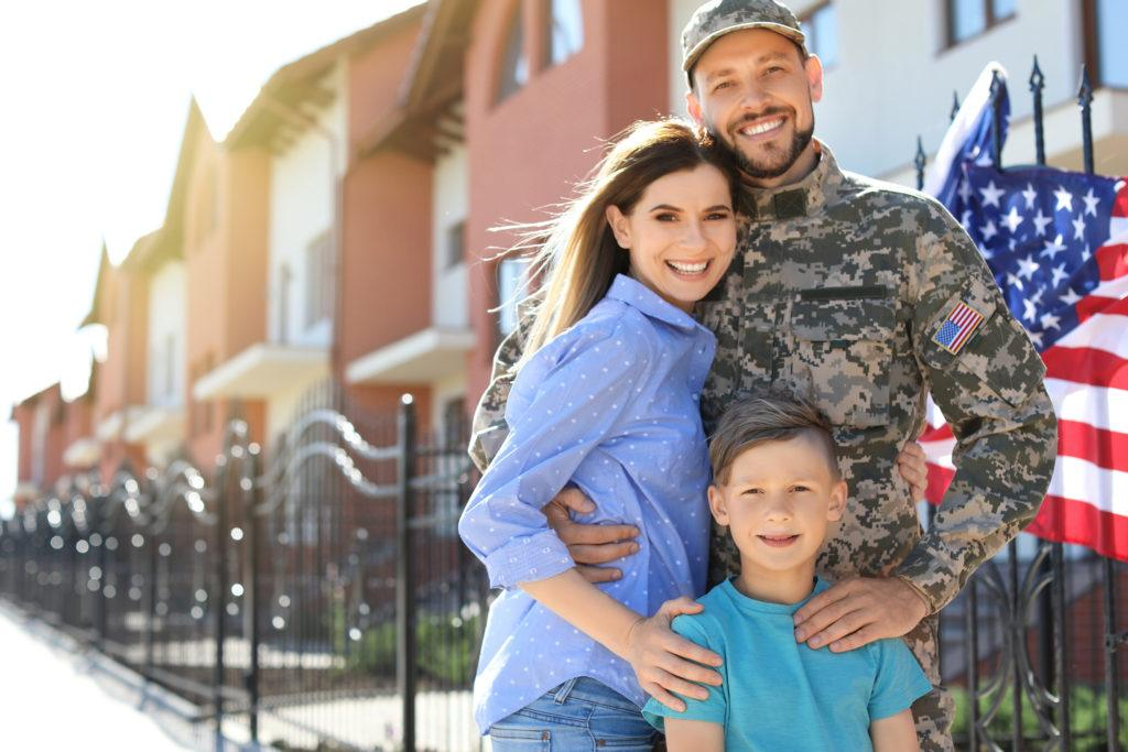 CBD assistance programs offer discounted rates on CBD oil products to veterans, the disabled, low income households, seniors, and other groups. Photo: A soldier with his family, including a wife and son, posing outside a row of apartments with an American flag.
