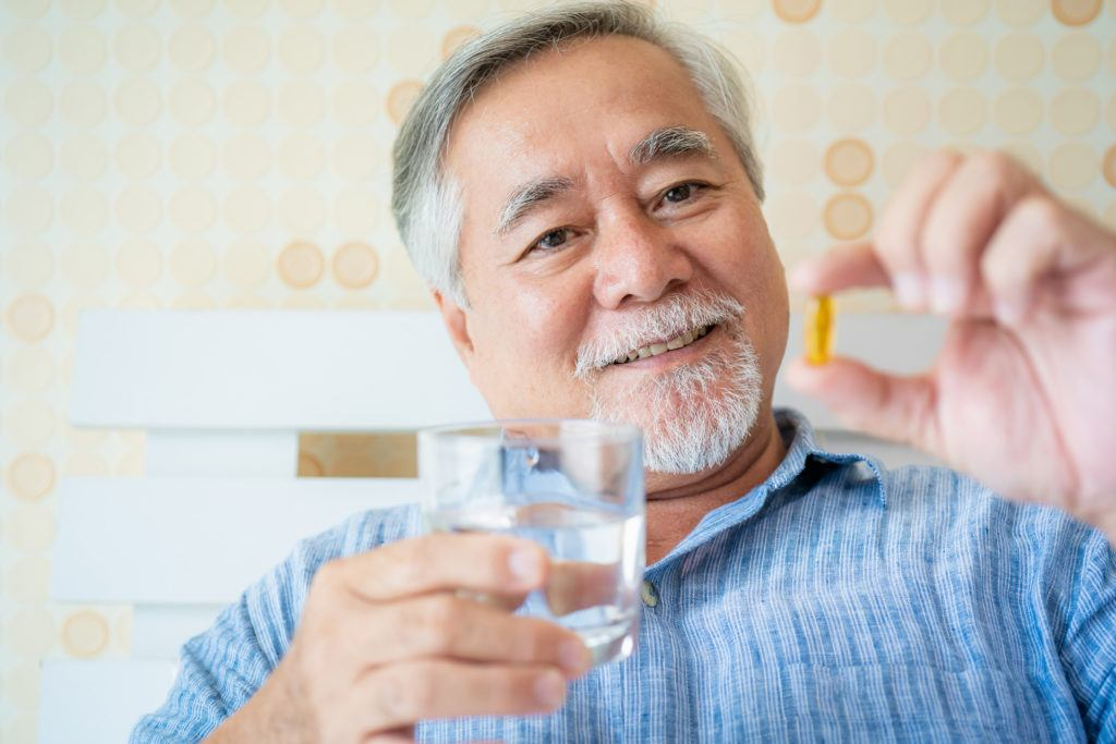 From reducing inflammation to helping balance the endocannabinoid system, we took a closer look at the anti-aging properties of CBD. Photo: A mature man holds up a supplement capsule, smiling, with a glass of water in the other hand.