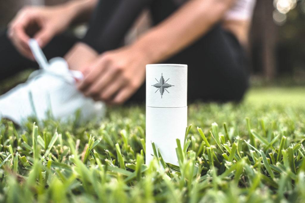 Canvas 1839 Relief Oil impressed us by offering pure, unadulterated CBD oil relief. Photo: A cardboard tube containing Canvas 1839 Relief Oil rests in the grass outside, with a person sitting in the background behind them.