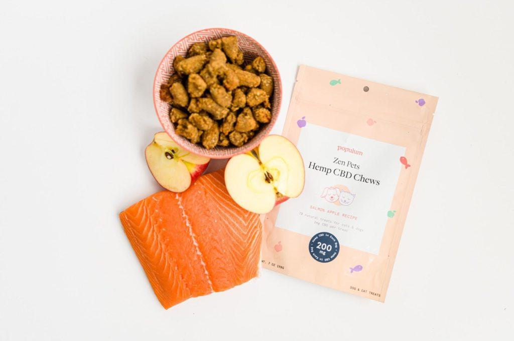 We were impressed by the quality ingredients in Populum Zen Pet Hemp CBD Chews. Photo: Populum Zen Pets Hemp CBD Chews in a bowl, and pouch, posed with key ingredients from the treats: salmon and apple halves.