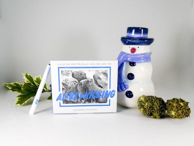 Alive & Kicking Slim CBD Pre-Rolls posed with buds of hemp flower and a ceramic snowman.