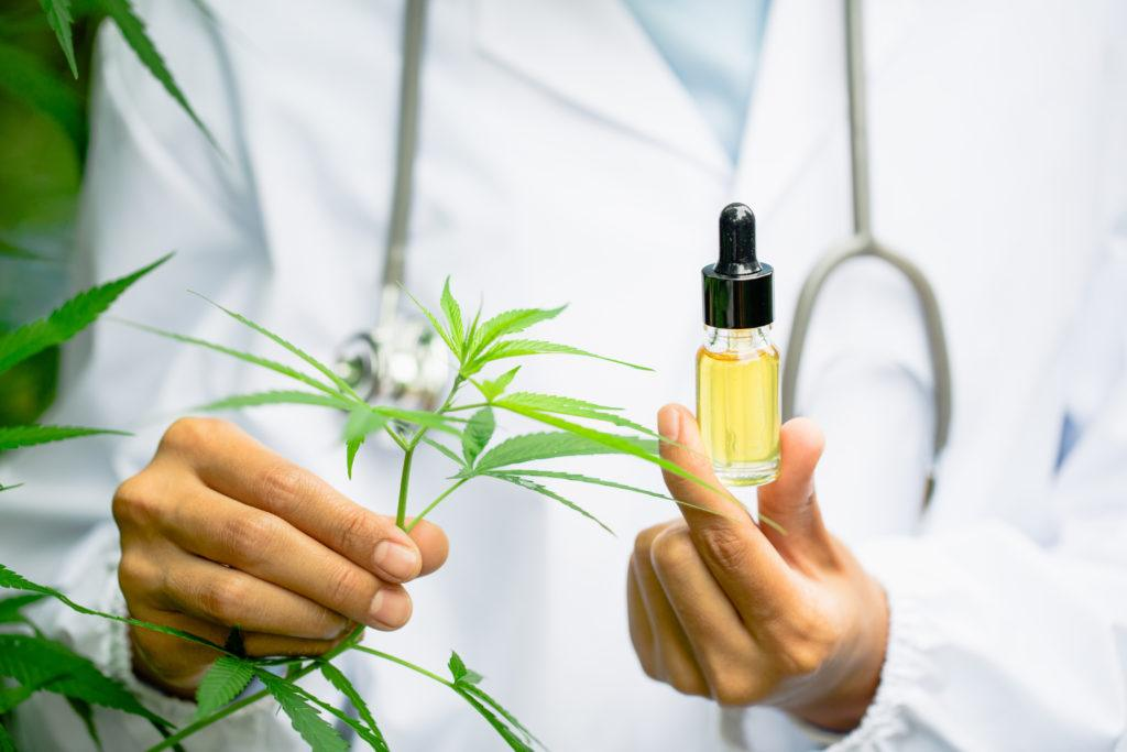 Epidiolex, a prescription epilepsy drug based on CBD, complicates the FDA's treatment of over-the-counter CBD supplements. Photo: A researcher in a lab coat and stethoscope holds a hemp leaf in one hand and a bottle of hemp extract in the other.