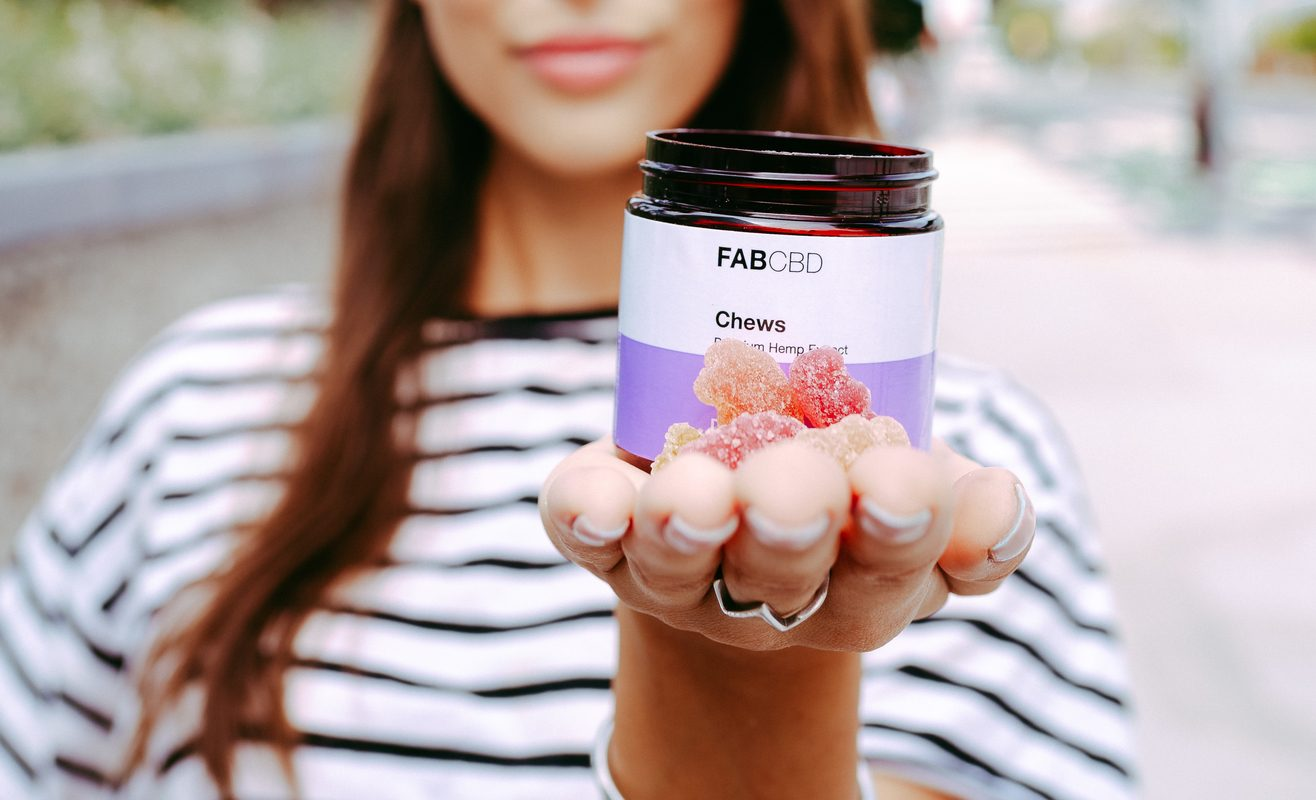 A woman holds Fab CBD Chews in her outstretched hand, including the jar and individual gummies.