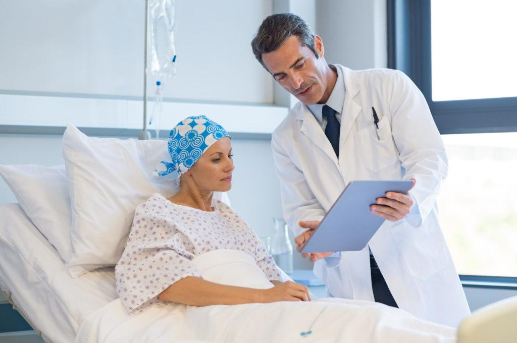 While rare, CBD can interfere with a few medications. It's always important to consult with a medical professional before adding CBD to your cancer treatment. Photo: A doctor consults with a woman in a hospital bed, holding a clipboard. She has a hair wrap on due to cancer treatment hair loss.