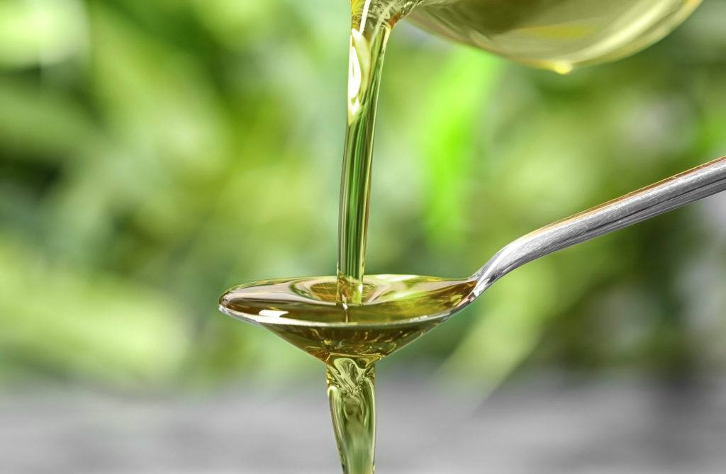 Photo: Hemp seed oil is poured onto an overflowing spoon from above. The background is blurry but green and organic.