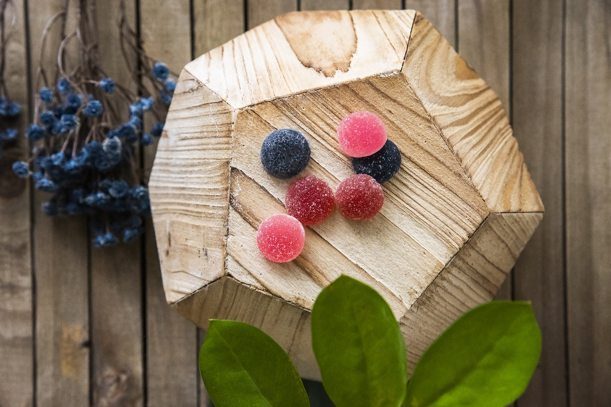 Photo: Wana Wellness Hemp Gummies in Berry Medley flavoers, posed on a wooden display stand, decorated with flowers and leaves.