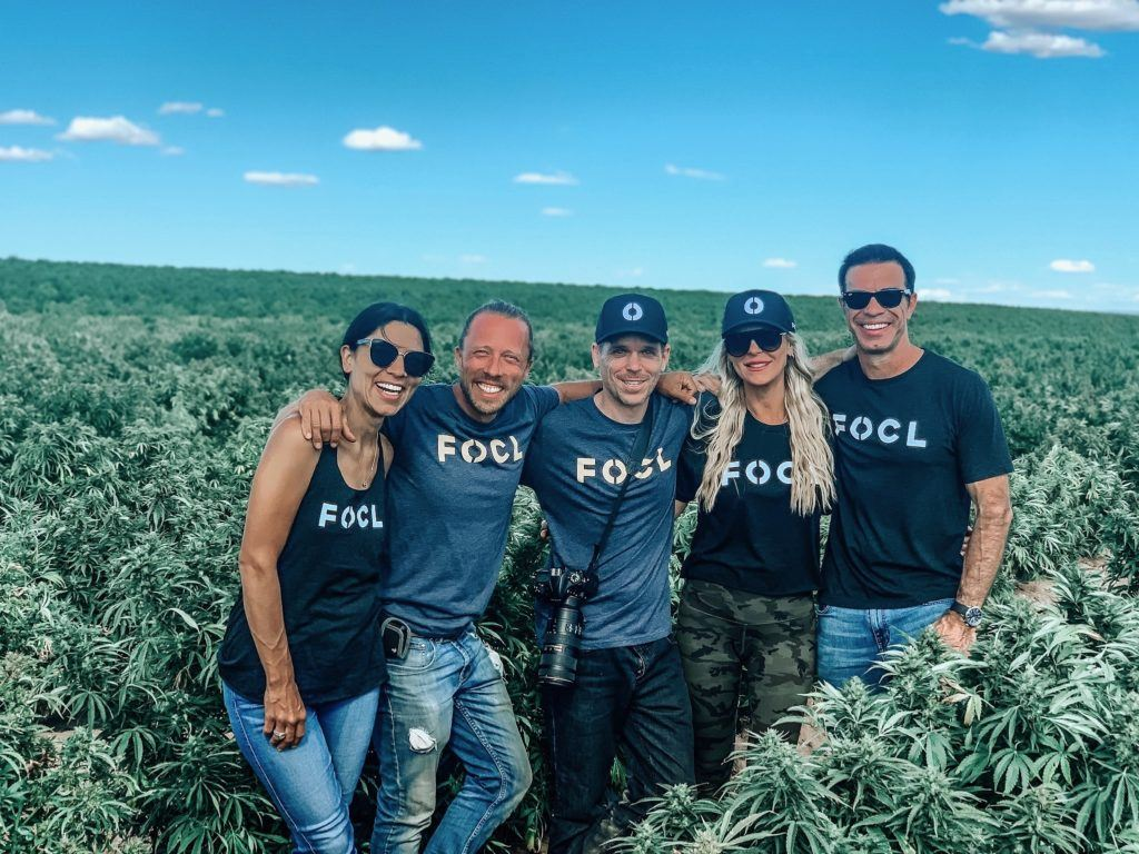 Photo: The FOCL team, including Ken Lawson, poses in a tall outdoor hemp field.