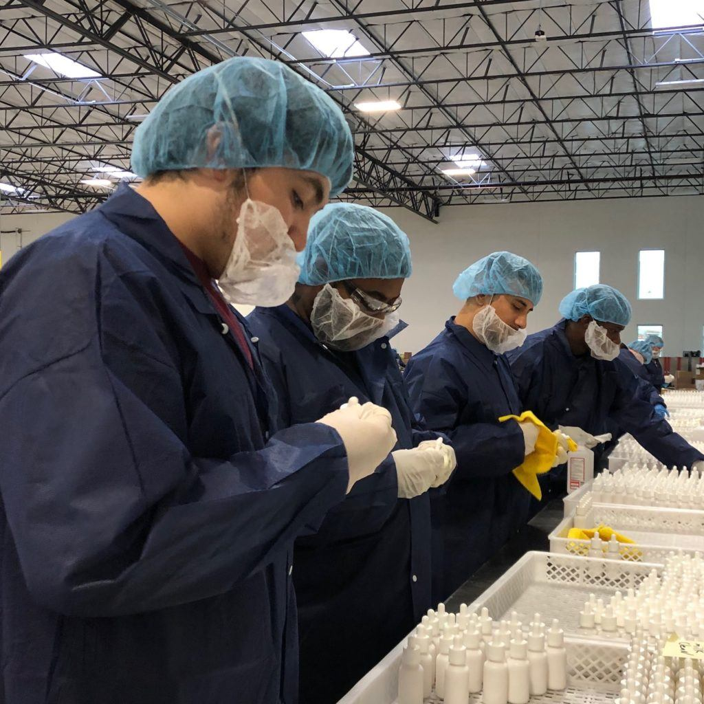 With a white label CBD business, your supplier creates products tailored to your needs and you focus on marketing them to your customers. Photo: An assembly line of workers in protective gear carefully creates white label CBD products.