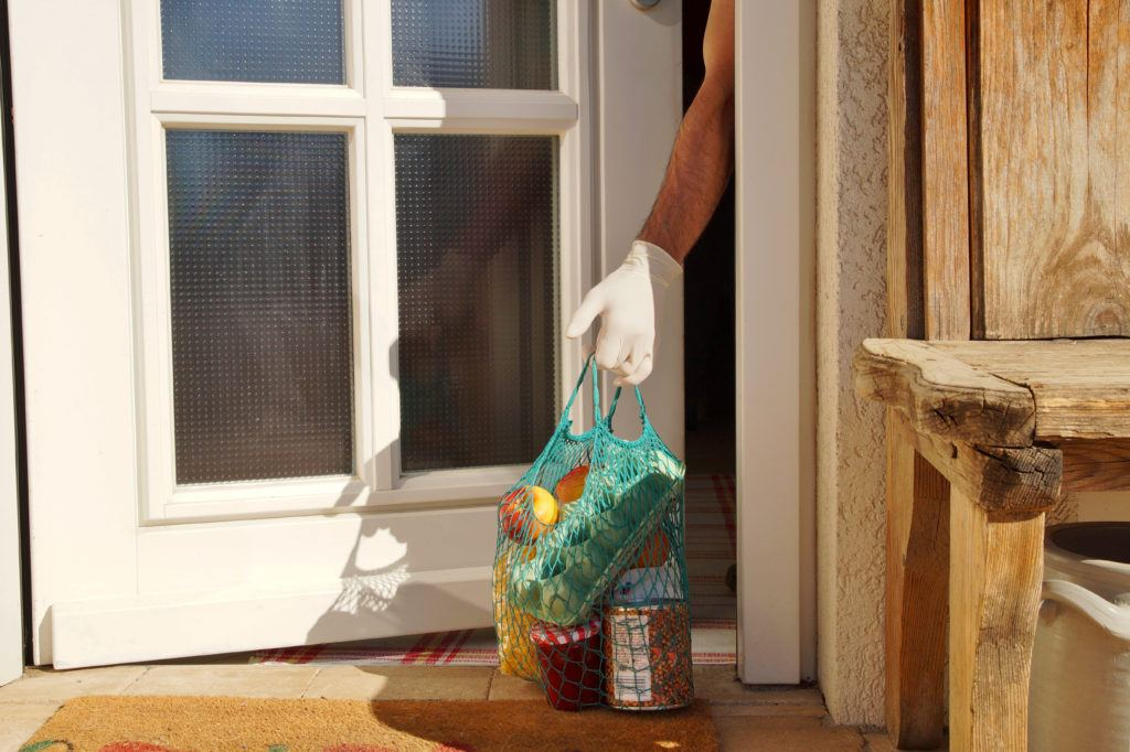 Photo: A hand, leaning out of an open door and wearing a disposable glove, picks up a mesh bag of groceries from a back porch.